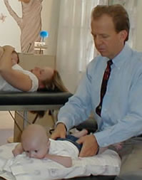 Darrel Crain - Chiropractor checking an infant