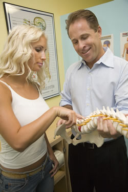 patient pointing to lumbar vertebrae - chiropractic