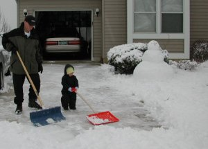 chiropractor shoveling snow with the kids
